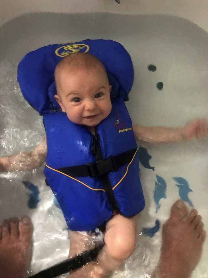 baby floating in infant life jackett PFD